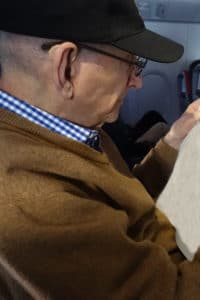 Senior man with hearing aids and reading glasses on airplane