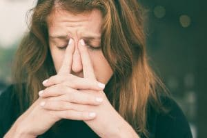 Tired Young Woman with Fingers on her Nose Bridge
