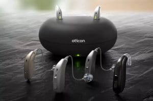 4 Oticon hearing aids in front of a hearing aid charging bay
