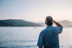 Man looks out at lake.