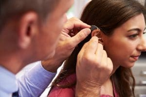 Woman gets hearing aid fitted.